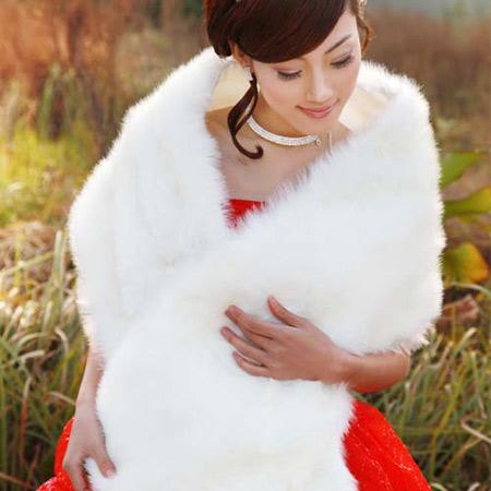 Một chiếc khăn choàng màu trắng vừa giữ ấm cho cô dâu trong ngày lạnh, vừa phù hợp với váy cưới đỏ.