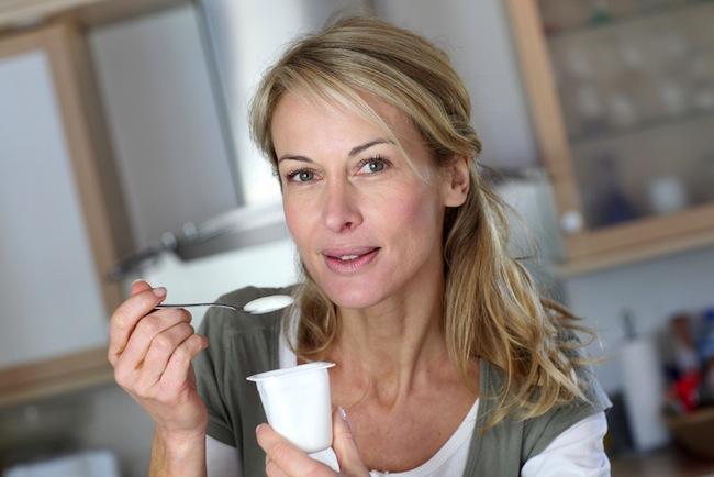woman eating yogurt in kitchen