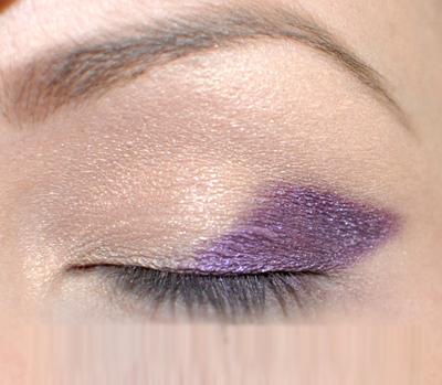 Phủ phấn mắt màu tím lên 1/2 đuôi mắt theo hình quả trám. Lưu ý, phía đuôi mắt đánh đậm hơn một chút để tạo độ sâu